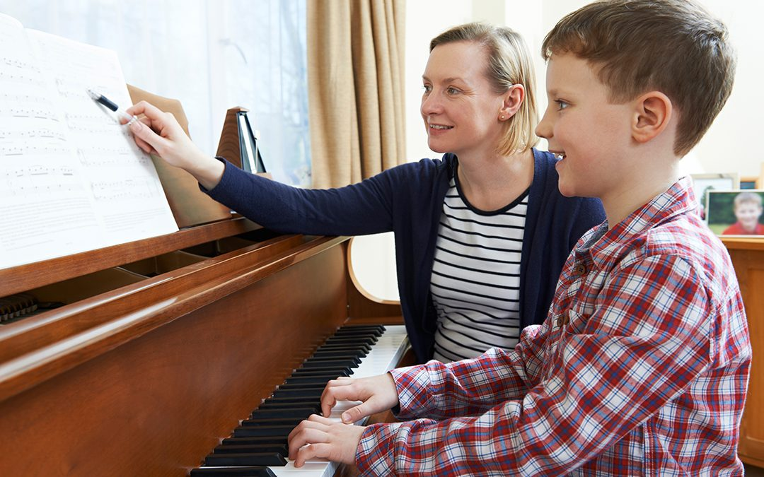 Boy With Piano Teacher Having Lesson At Piano