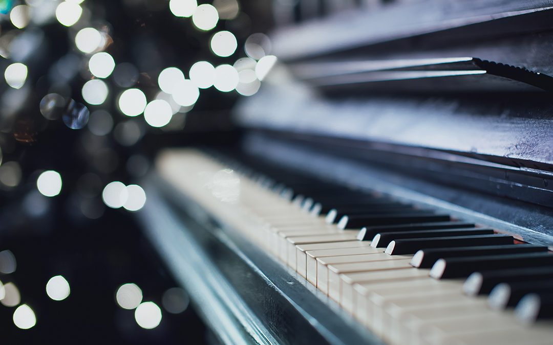 Closeup of used grand piano with lights twinkling in background